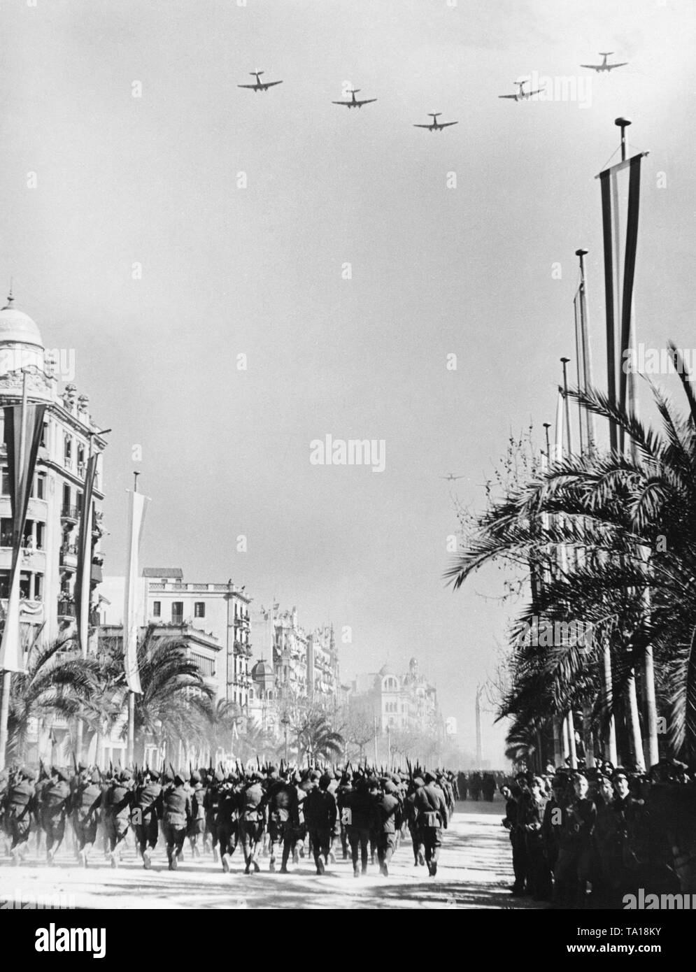 Photoof a victory parade of Spanish nationalunits on Passeig de Colon after the conquest (January 1939) of Barcelona by General Francisco Franco in February, 1939. In the foreground, marching infantry units. In the sky, formation flight of the German Condor Legion. - Stock Image
