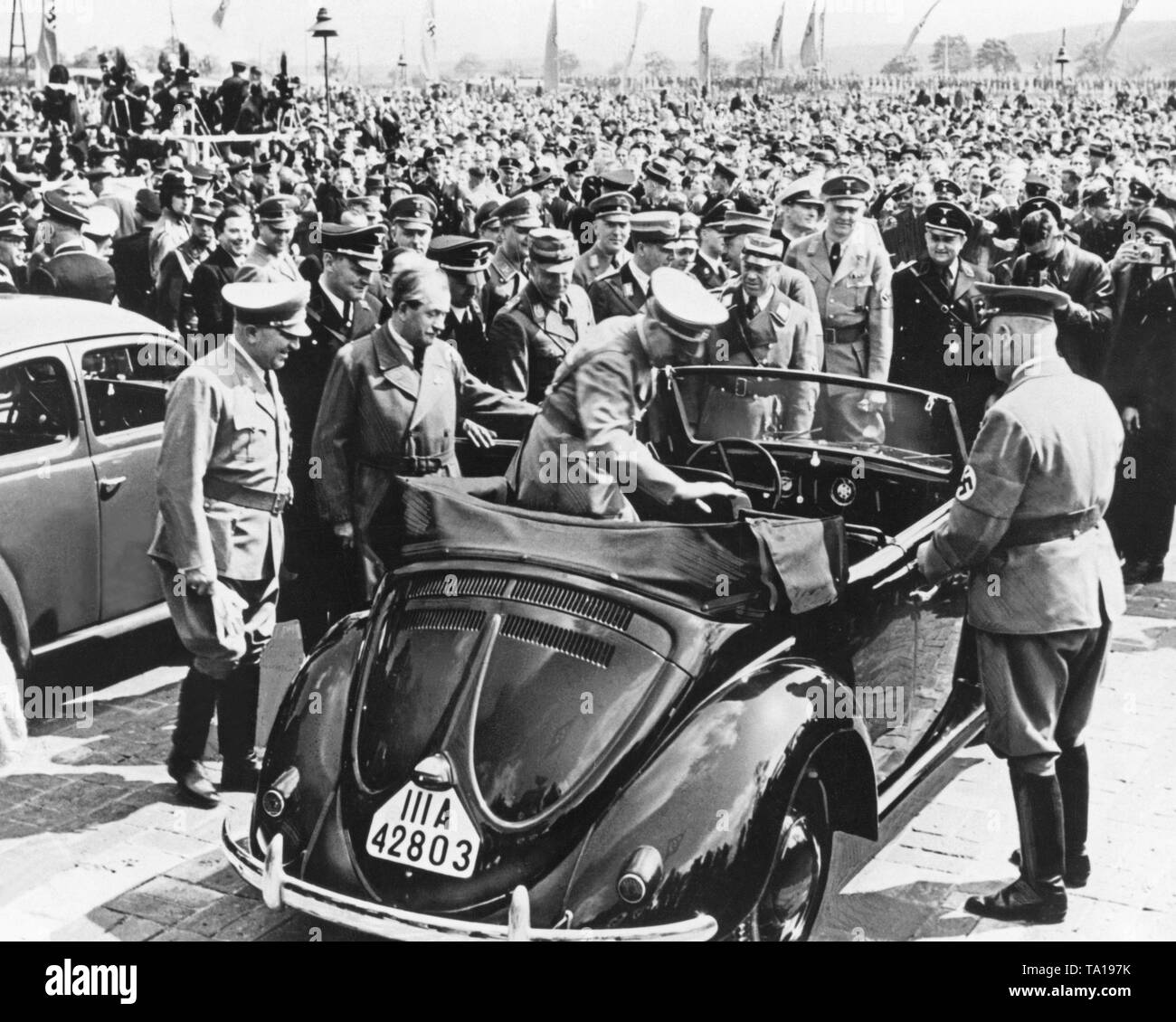 Adolf Hitler gets in a prototype of the VW Beetle Convertible. Behind Hitler, the designer of the Beetle, Prof. Ferdinand Porsche. To the left of Porsche is the Chief of Staff if the SA Viktor Lutze, the Reich Leader of the NSDAP Robert Ley, Adolf Huehnlein and Alfred Rosenberg. - Stock Image