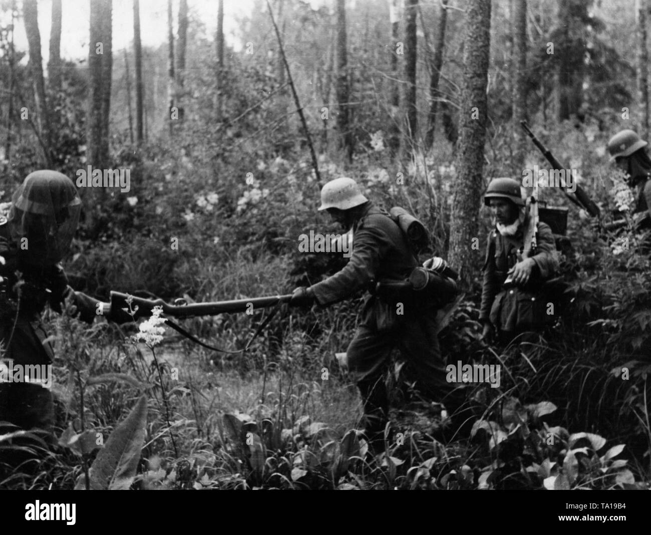 German infantry crosses a marshland east of Kowel. The soldier on the left carries a mosquito net over his helmet. Stock Photo