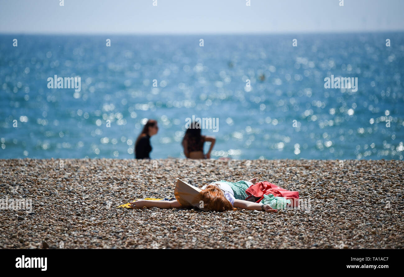 Brighton UK 21st May 2019 - Visitors enjoy the warm sunny weather on Brighton Beach today with it forecast get get warmer over the next couple of days throughout Britain . Credit : Simon Dack / Alamy Live News - Stock Image