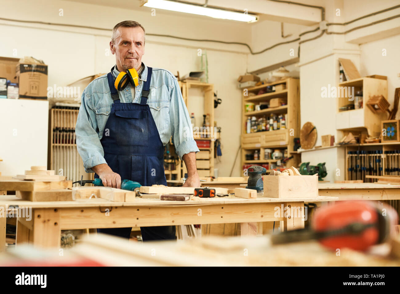Waist up portrait of senior carpenter looking away while working in joinery, copy space - Stock Image