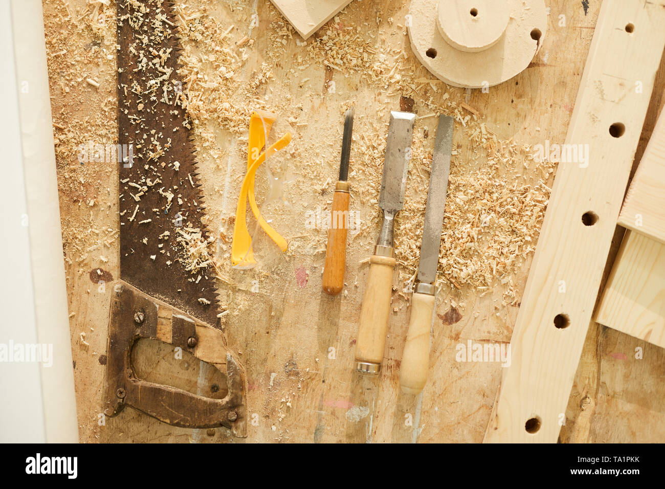 Above view background of carpenters tools on table in workshop dusted with wood shavings, copy space - Stock Image