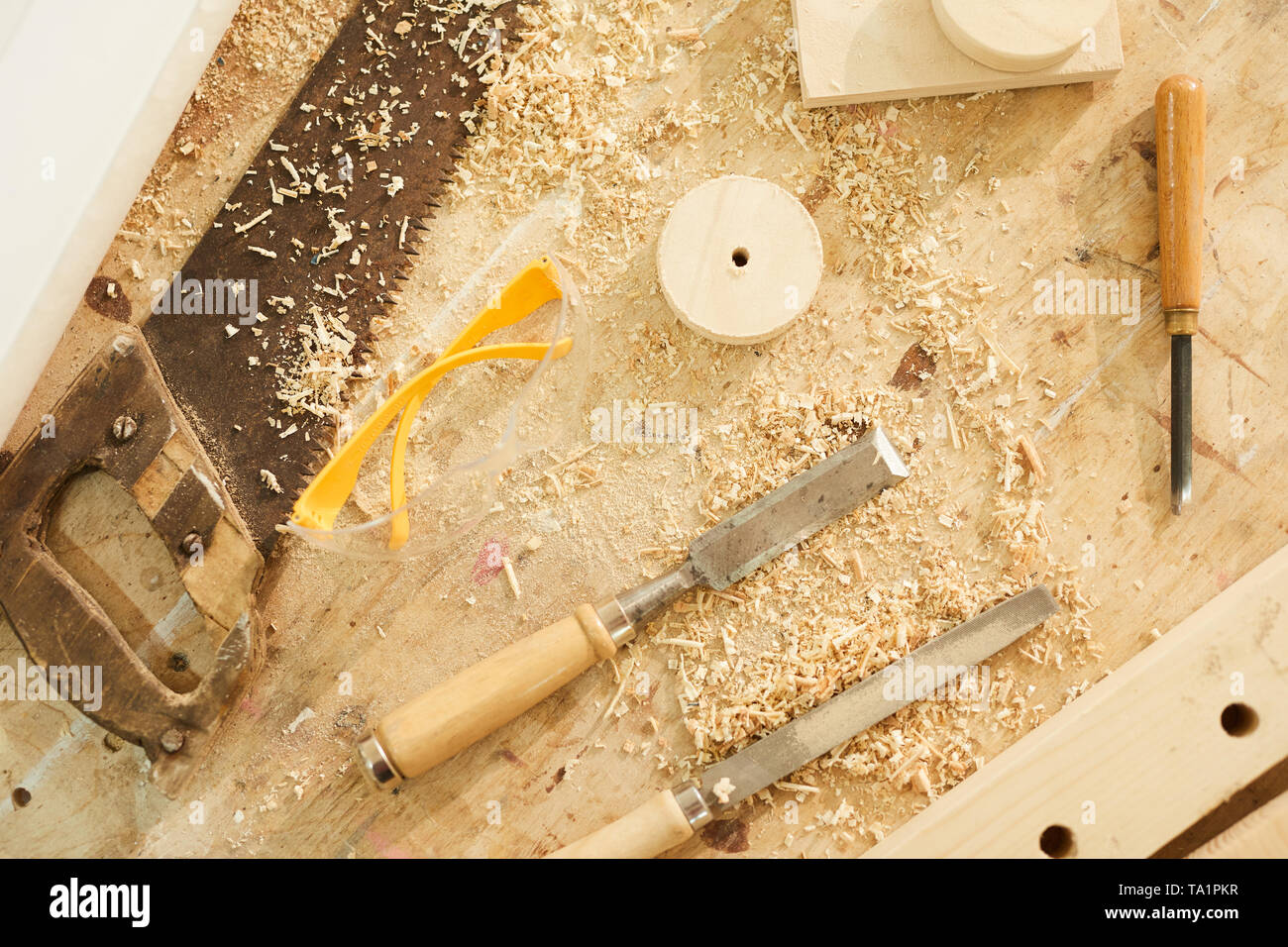 Top view background of carpenters tools on table in workshop dusted with wood shavings, copy space - Stock Image