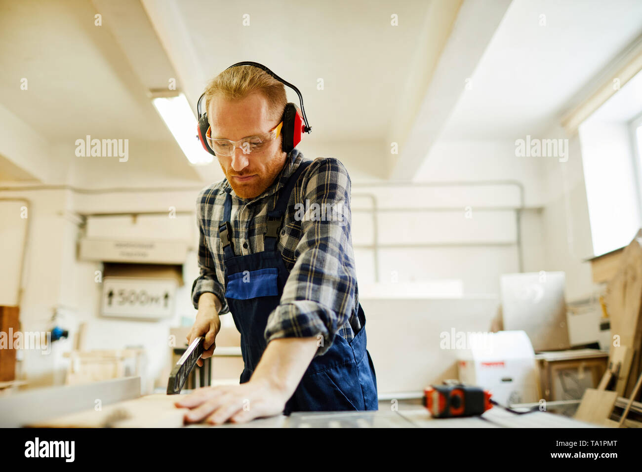 Waist up portrait of contemporary carpenter cutting wood while working in joinery, copy space - Stock Image