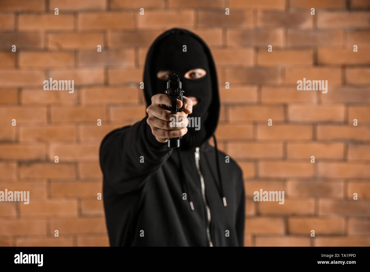 Male criminal pointing a gun at viewer against brick background - Stock Image