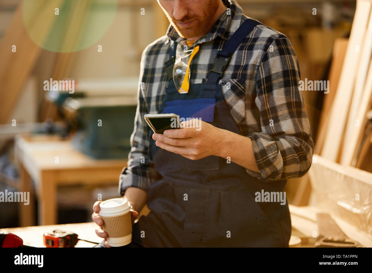 Mid section portrait of modern carpenter using smartphone during coffee break in joinery, copy space - Stock Image