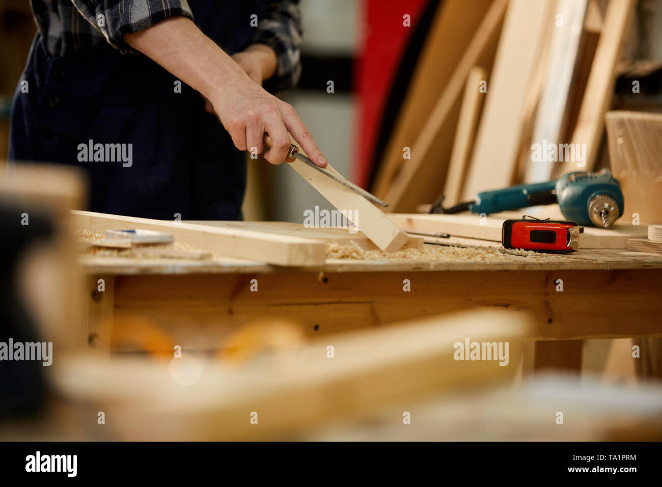Closeup of unrecognizable carpenter carving wood while working in joinery lit by sunlight, copy space - Stock Image