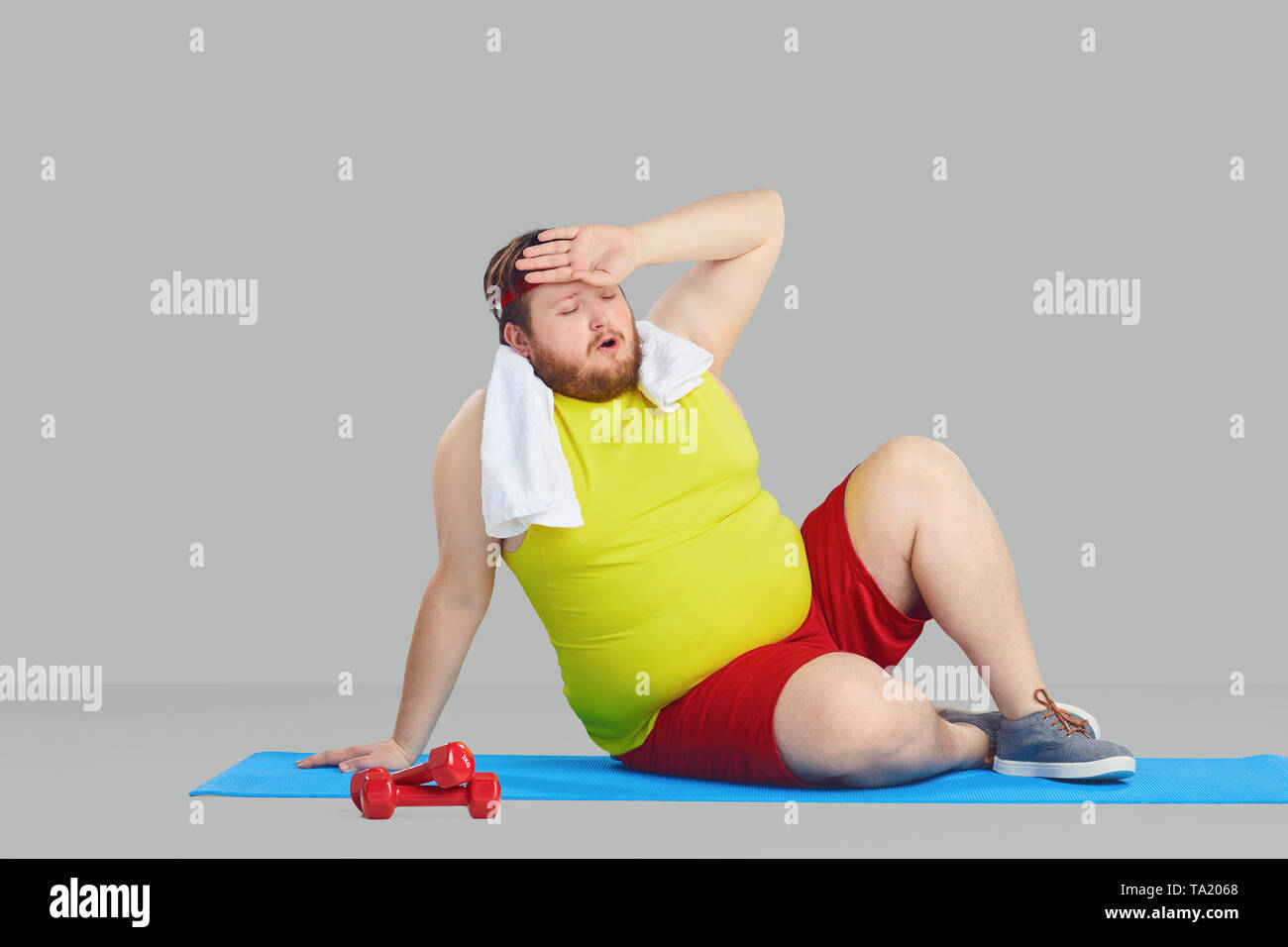 A fat man in sportswear tired wipes the sweat from his forehead sitting on the floor against a gray background. - Stock Image