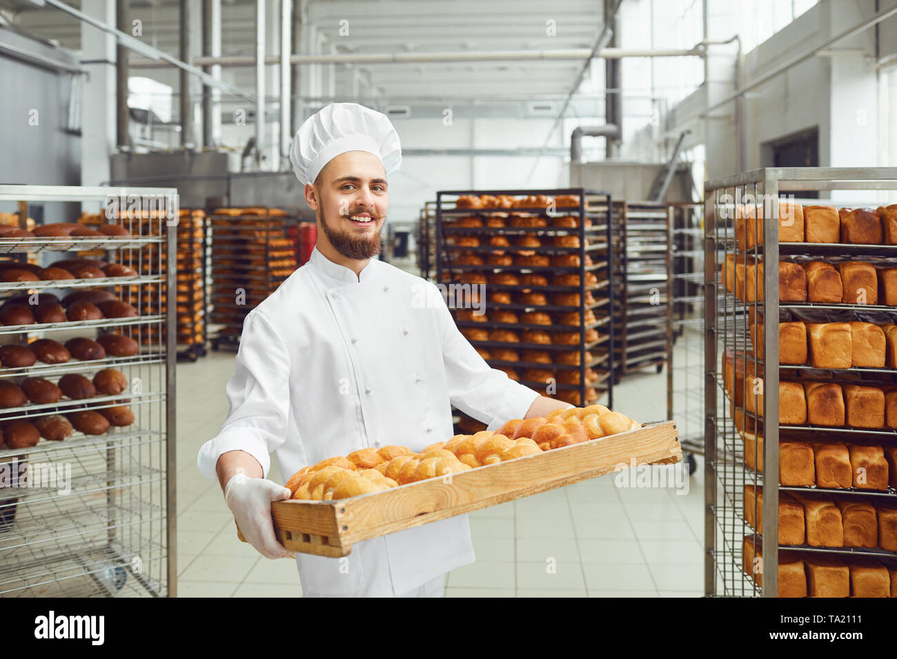 Smiling baker in white uniform with trays of fresh bread costs in the production of the bakery. Stock Photo