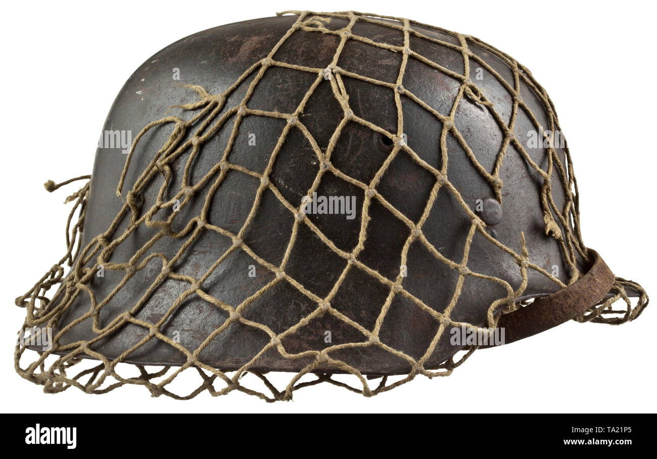 A steel helmet M 42 for army personnel with camouflage netting Steel skull with field-grey paint, maker stamping 'ckl 66' (Thale Iron Works), the emblem up to 80% intact, complete inner liner with chin strap, the helmet's netting for attachment of camouflage material with a few blemishes. historic, historical, army, armies, armed forces, military, militaria, object, objects, stills, clipping, clippings, cut out, cut-out, cut-outs, 20th century, Editorial-Use-Only - Stock Image