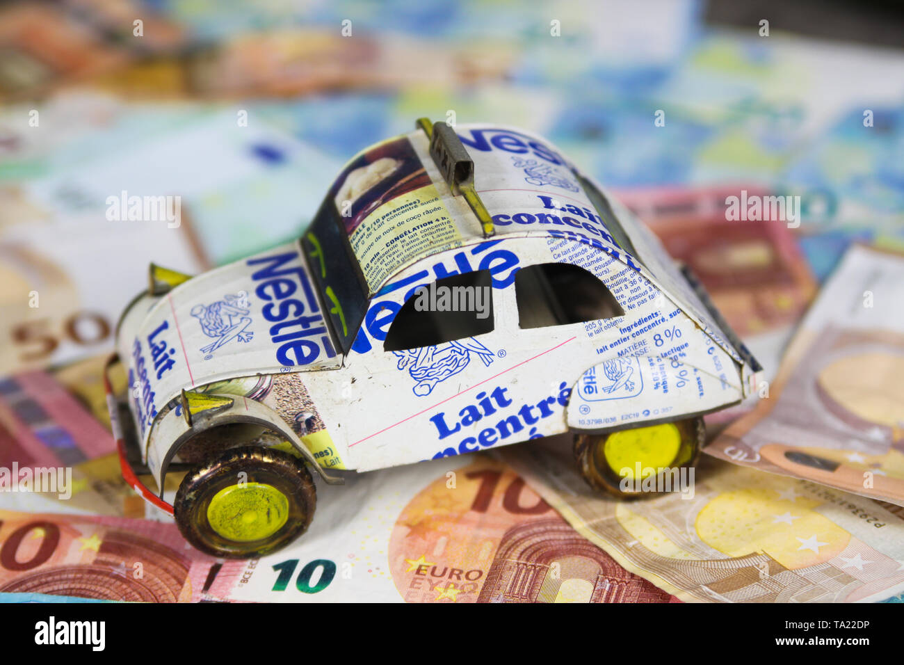 VIERSEN, GERMANY - MAY 20. 2019: Annual vehicle car cost concept - Model of car made of recycled cans on Euro paper money bank notes Stock Photo