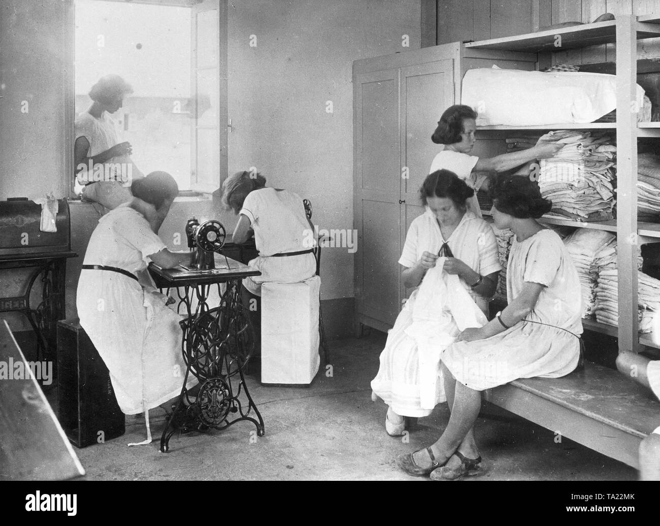Six women work in a tailor's workshop making children's clothing in a Jewish colony. - Stock Image