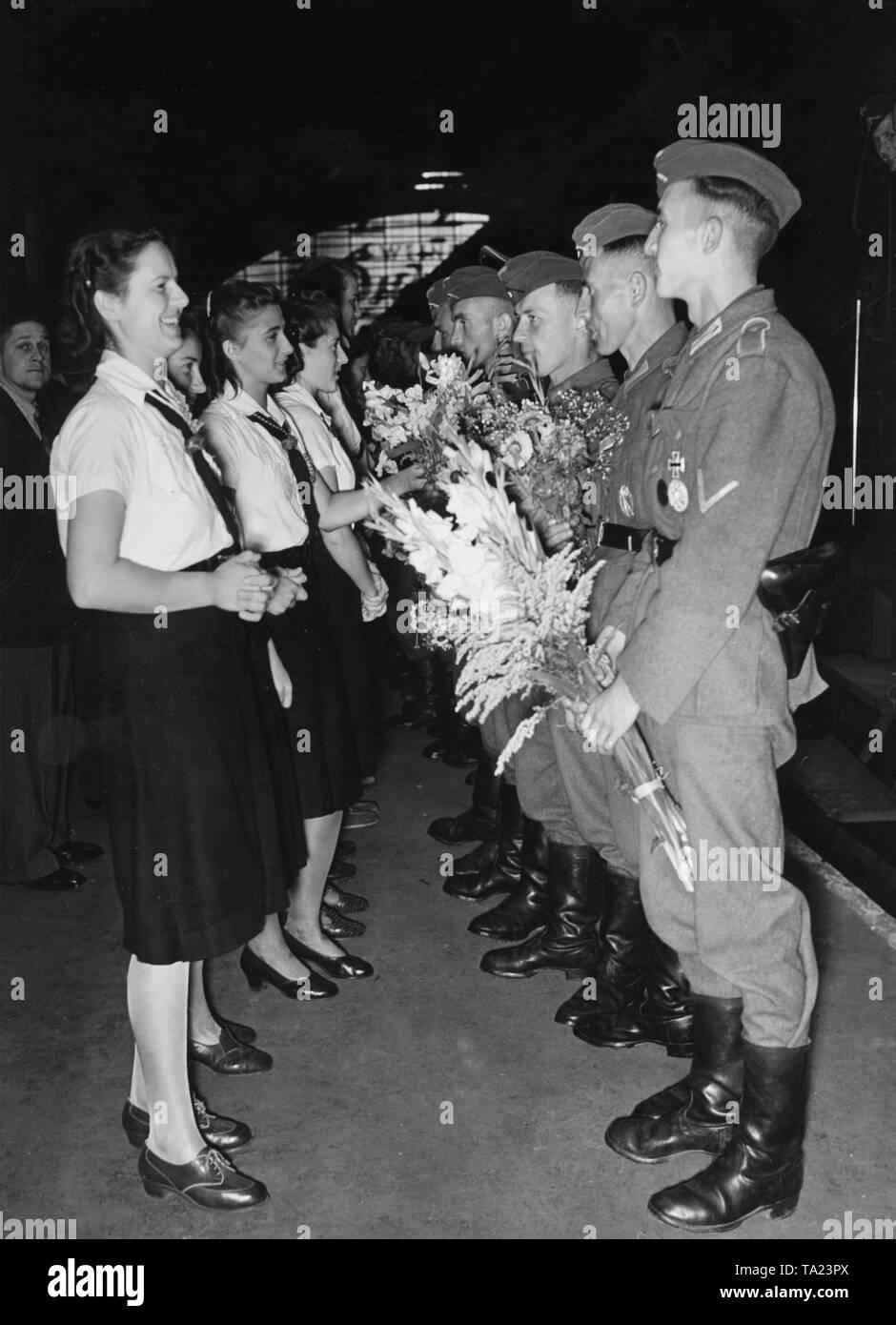 BDM girls hand over bouquets of flower to returned soldiers from the Crimea. - Stock Image
