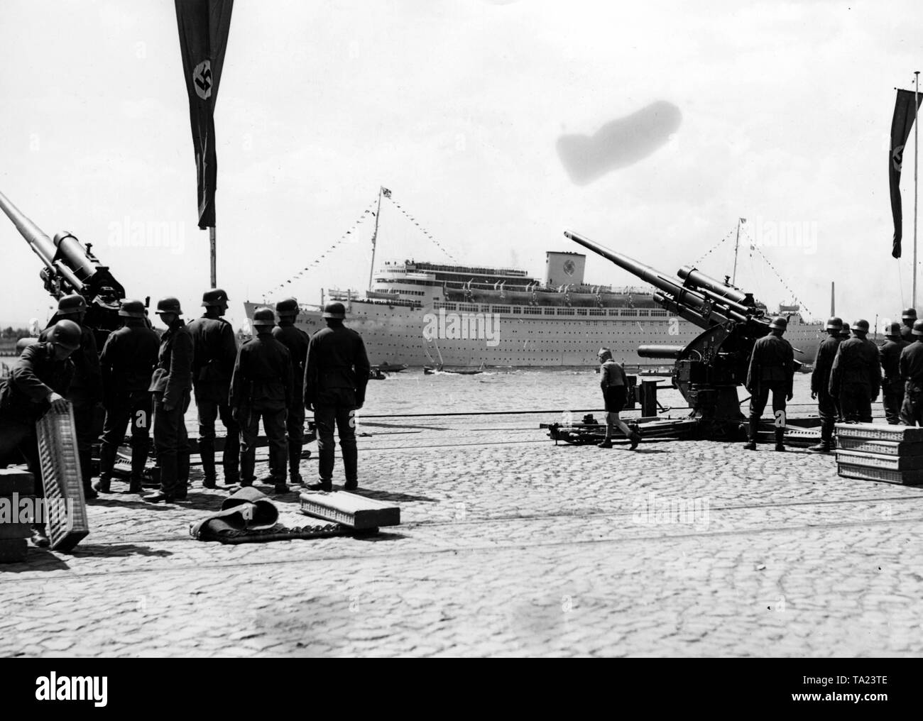 As the flagship of the KdF fleet 'Robert Ley' with the staff of the Condor Legion and Wolfram von Richthofen on board, passes by Neumuehlen and the gangways of Hamburg, the salute batteries of a Flakartillerie 8.8cm FlaK 36 (Antiaircraft artillery) of the Luftwaffe (German Air Force) are welcoming it. - Stock Image