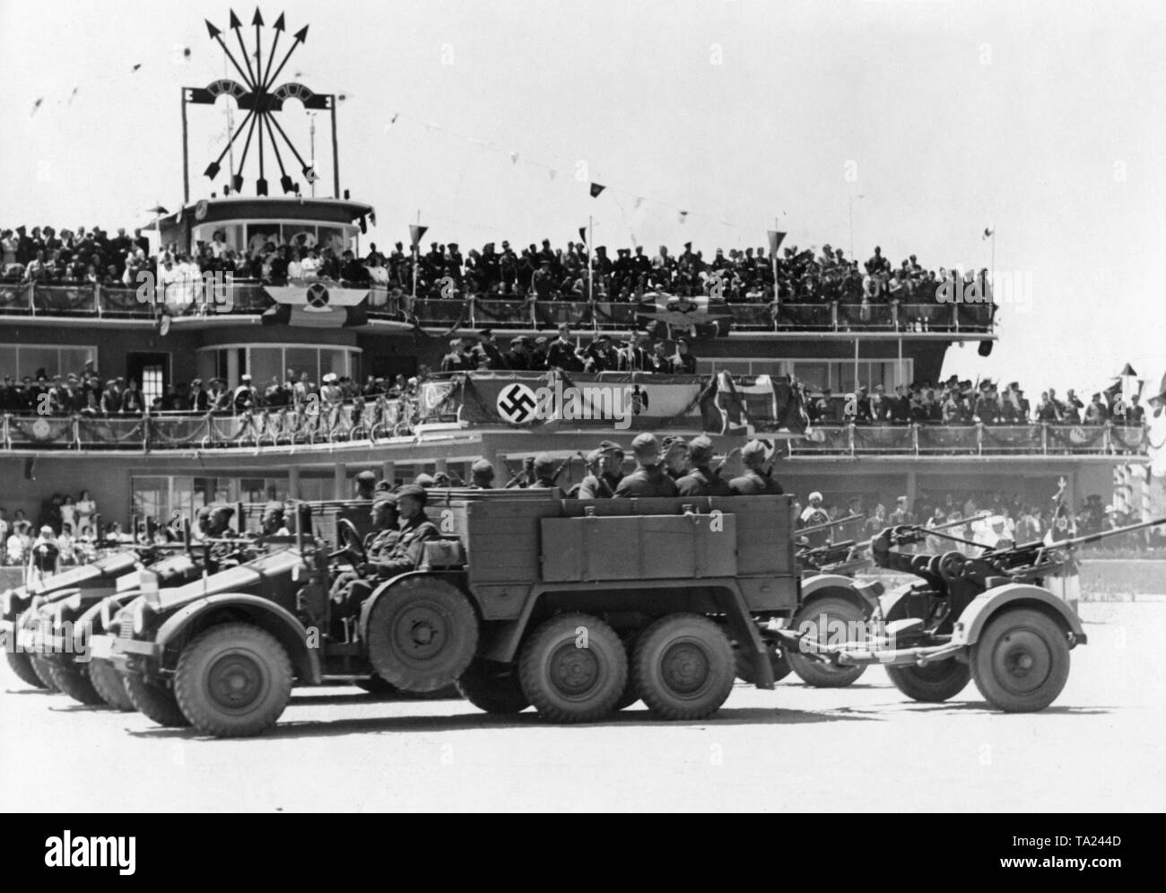 Photo of a German anti-aircraft unit of the Condor Legion (truck of the type Krupp L2 H143 with an attached 2cm flak 30) during a victory parade for General Francisco Franco at Barajas airport, Madrid, after the invasion of the city on March 28, 1939. In the background there is the terminal of the airport with the VIP stand for Franco and the symbol of the Fascist Party of Spain, the Falange (arrows and yokes). - Stock Image