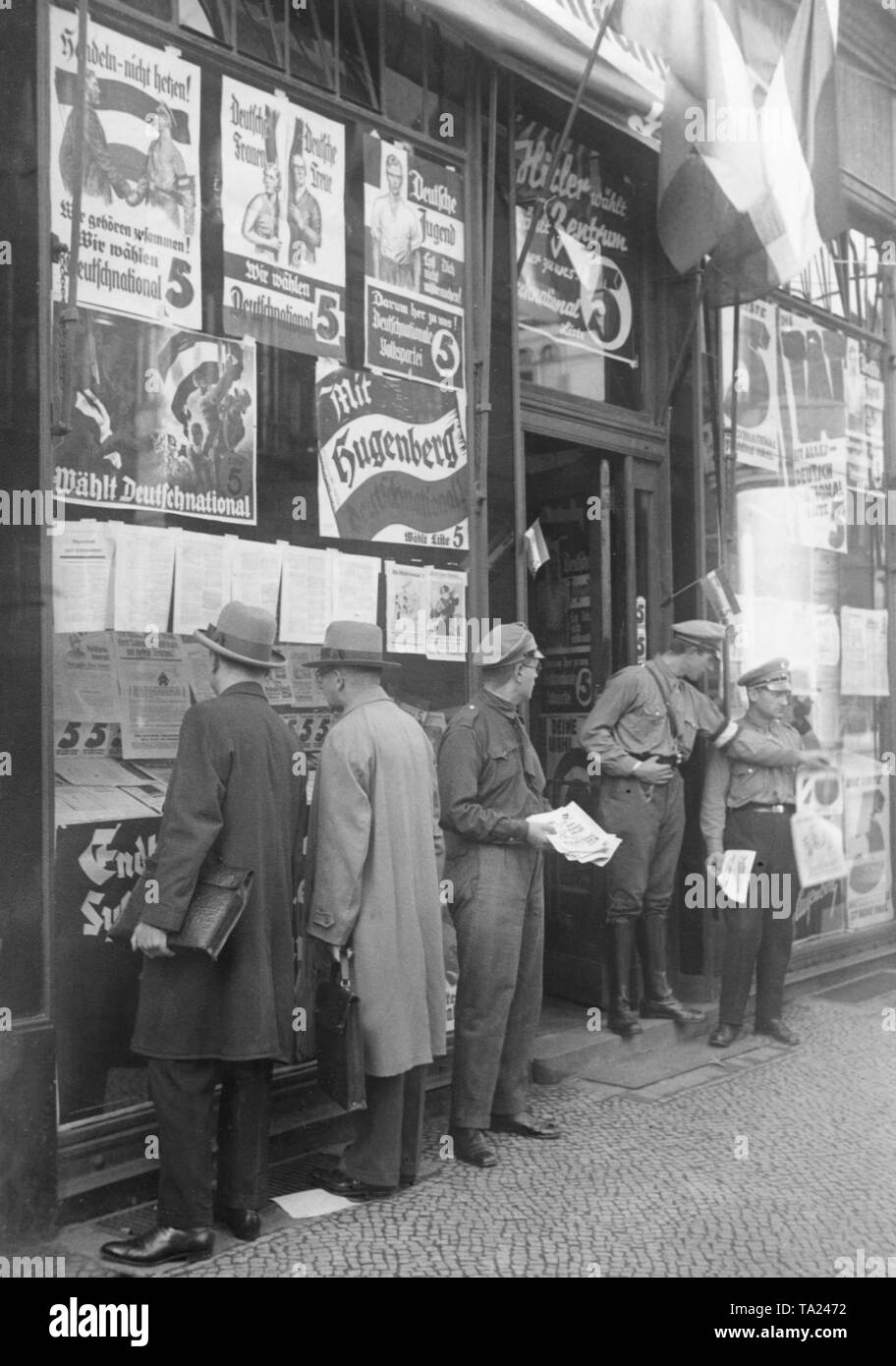 In the run-up to the Reichstag election in July, 1932, election campaigners of the DNVP (German National People's Party) distributed ballots in front of the party's propaganda shop in Neue Wilhelmstrasse 3. There are election posters displayed in the shop windows. Stock Photo