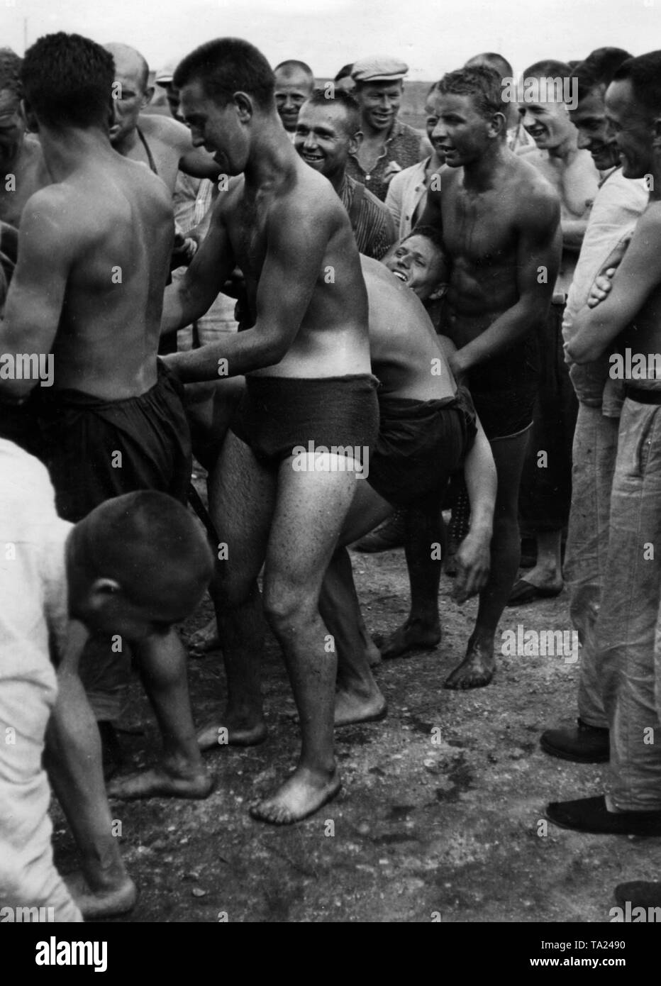 """People laugh and joke in a """"swimming pool"""" of the Dachau concentration camp, one of the propaganda photos of the NS regime. Stock Photo"""