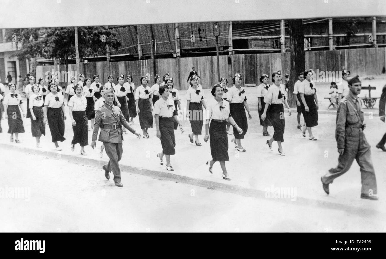 Photo of a group of marching women of Accion Ciudadana, a Spanish national civil movement, which was part of the CEDA (Spanish Confederation of Autonomous Right-wing Groups) until 1937. The photo was probably taken in Burgos, Castile and Leon, and shows women in white blouses and dark skirts with gorillo caps, on which a white cross was sewn. The women are accompanied by soldiers. On the left, an officer ranked comandante (Major). Stock Photo
