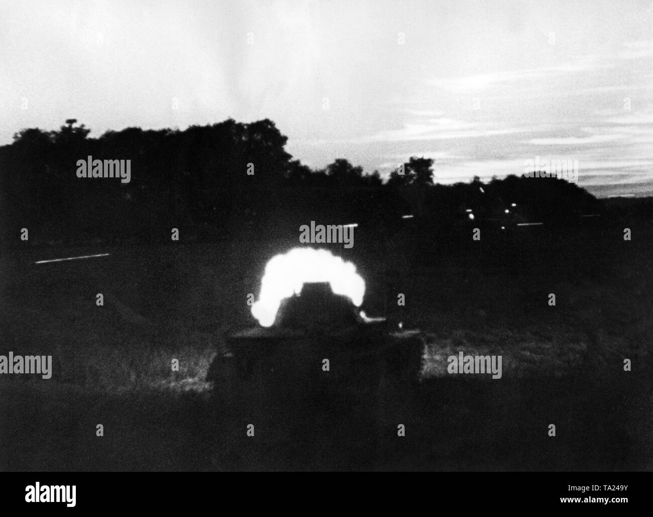 A German Panzer III opens fire during a night battle. Probably a moviestill from Sieg im Westen (Victory in the West). Stock Photo