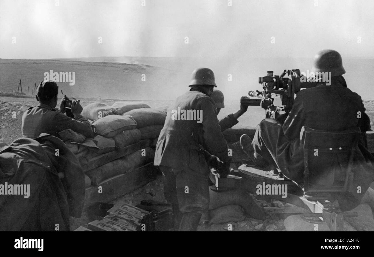 Undated photo of an antiaircraft unit of the Condor Legion during the deployment in the Spanish Civil War. Two men aim at ground targets with a 2cm FLAK 39 in a sandbag position. On the left in the front there are crates of ammunition. The soldiers are wearing M35 steel helmets. - Stock Image