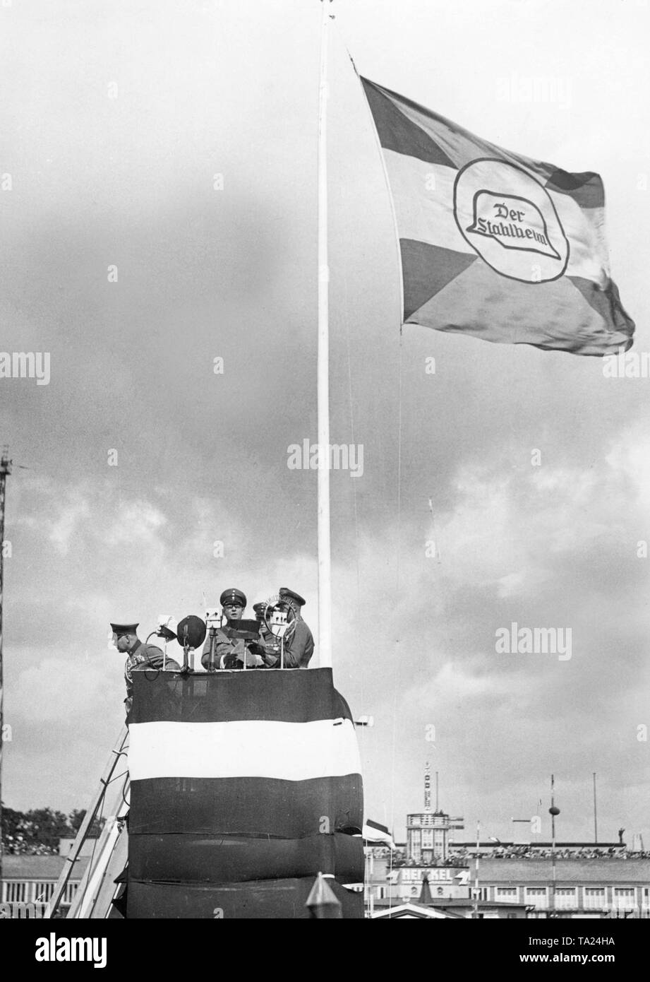 On the Tempelhof field the Stahlhelm is holding a demonstration at which a speech is held in several microphones from a tower-like podium. The podium is decorated with the black-white-red flag of the empire, on a flagpole is a flag with the symbol of the Stahlhelm. - Stock Image