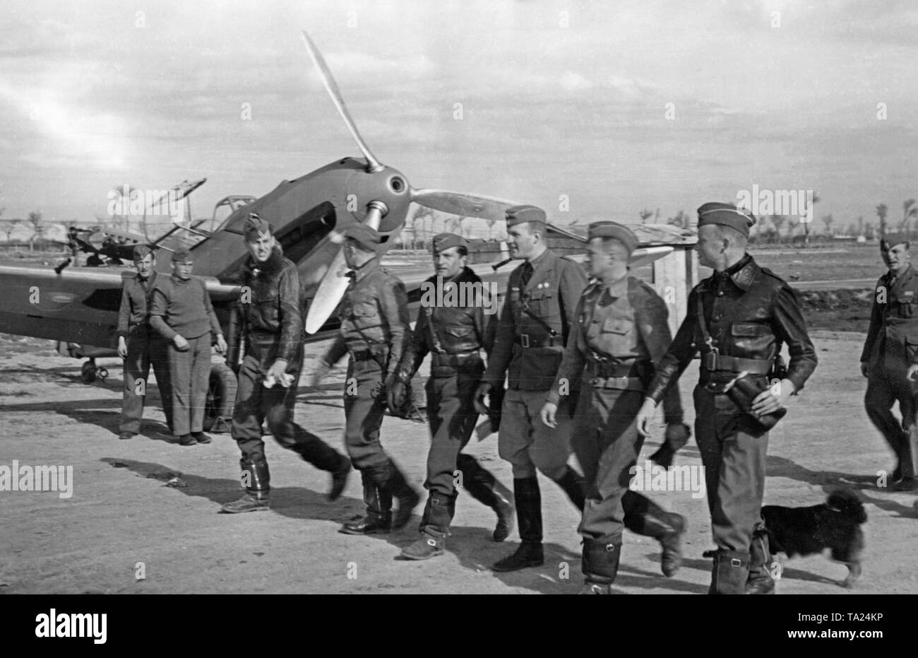 Photo of a group of combat pilots of the Condor Legion, fighting group 88, while marching to their ready-to-use Messerschmitt Bf 109 fighters (in the background) on an airfield in Spain in 1939. The mouth of the machine gun is visible in the hollow propellor nose cone. - Stock Image