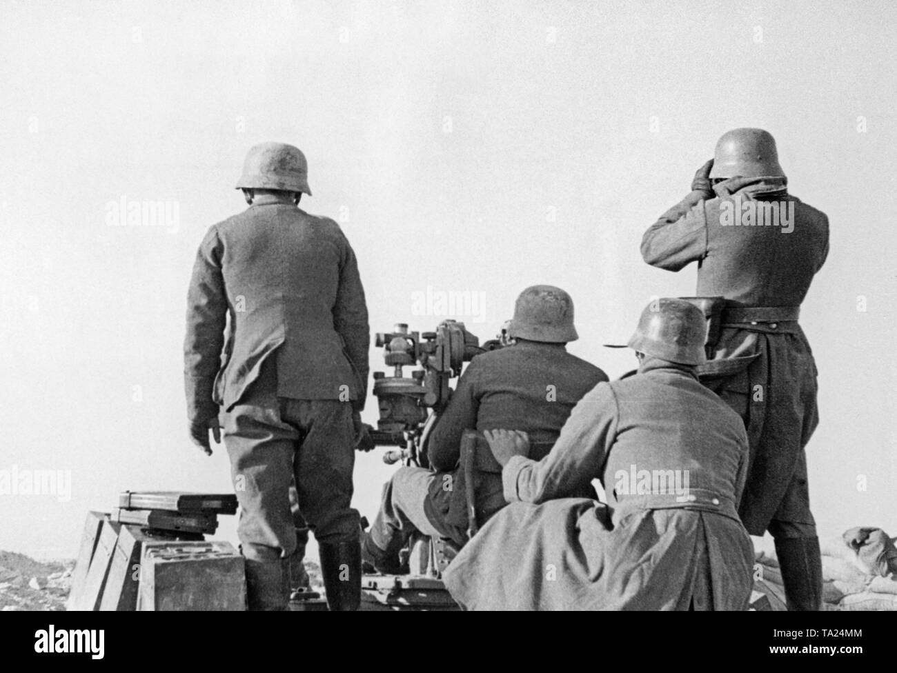 Undated photo of an anti-aircraft unit of the Condor Legion during a deployment in the Spanish Civil War. Two men are aiming at ground target using a 2cm FLAK 39 in a sandbag position. An officer (left) picks the targets. On the left in the front, there are crates of ammunition.The soldiers are wearing M35 steel helmets. - Stock Image