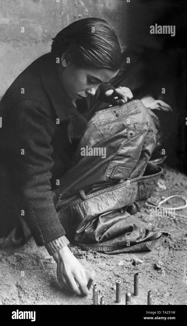 A boy playing with cartridge cases in the rubble during the Spanish Civil War. - Stock Image