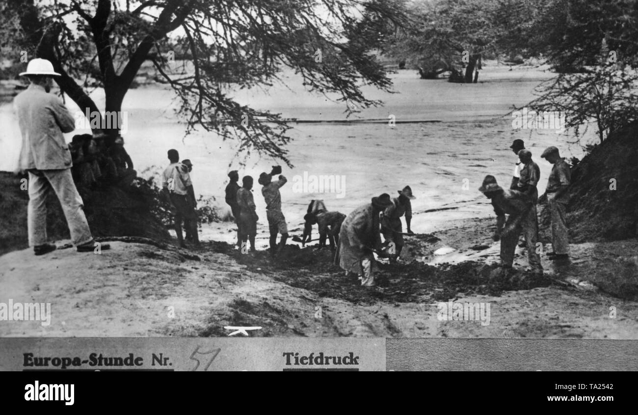 Workers stand on the edge of a flooded landscape during the rainy season on the territory of the former colony of German South West Africa and shovel a sand pit (undated shot). - Stock Image