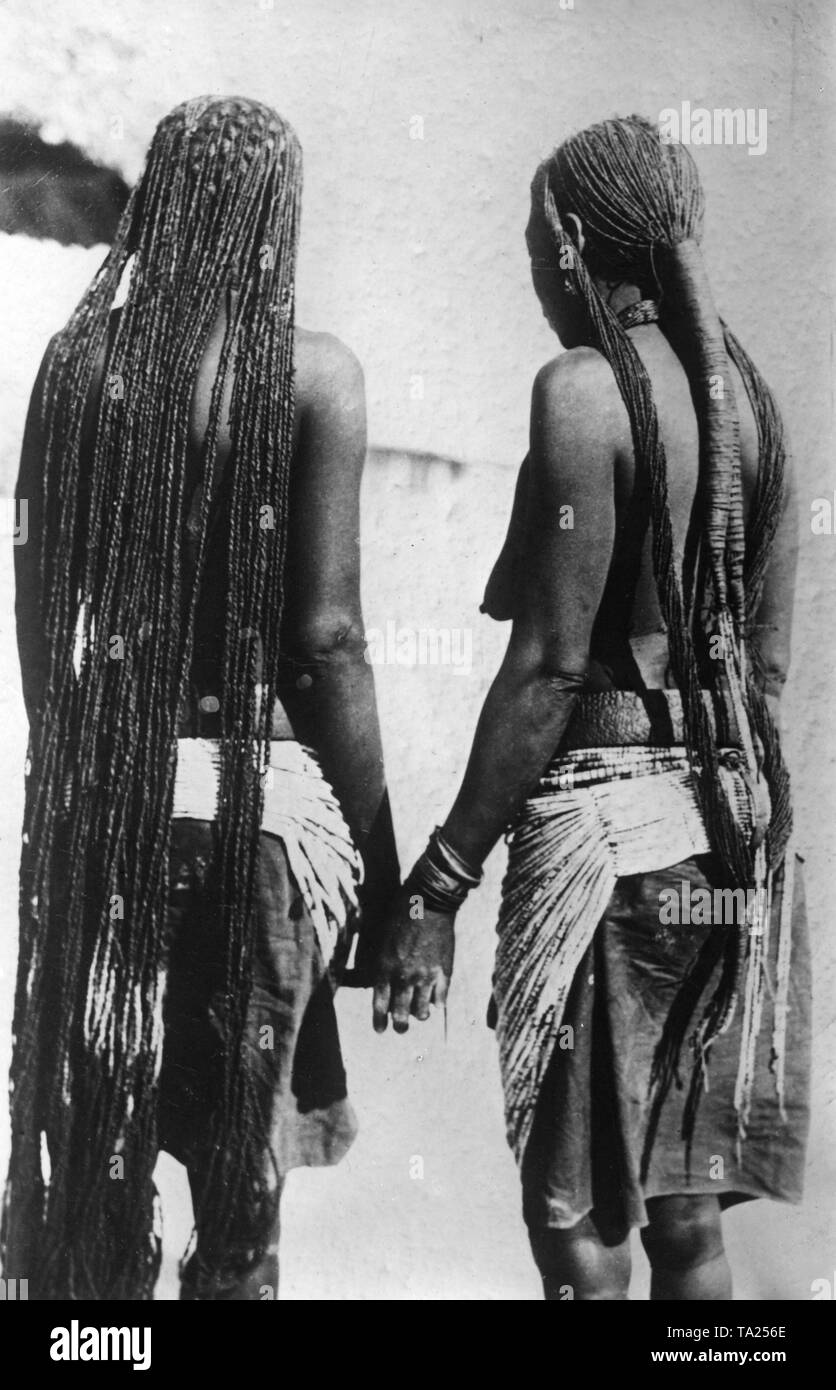 Two traditional Ovambo women wearing long braided hair in German Southwest Africa (undated shot). - Stock Image