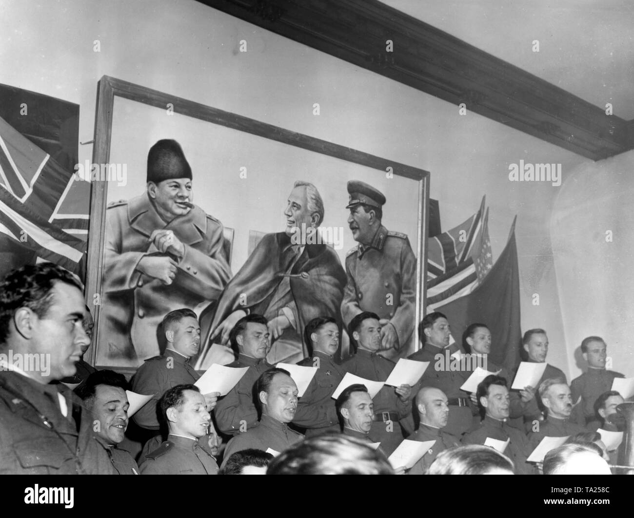 A Russian soldiers' choir sings at the Soviet headquarters on the occasion of the meeting with American troops. In the background a picture showing the heads of state of the Allied nations (from left: Churchill, Roosevelt, Stalin) at the Yalta conference. Stock Photo