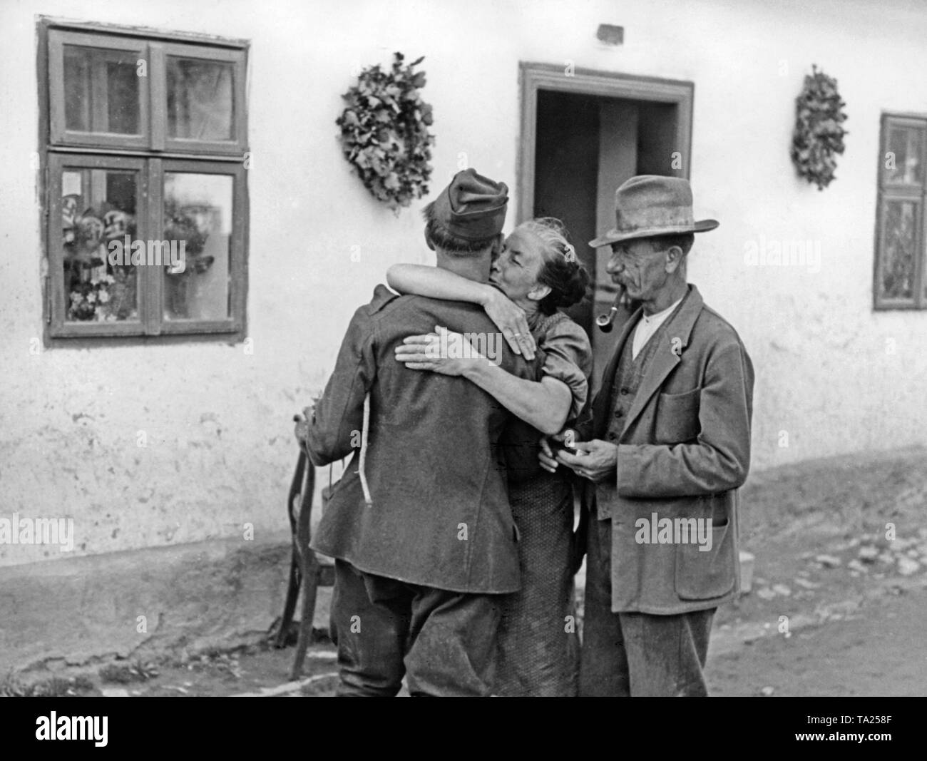 A soldier from the Sudetenland, who was given discharge from the Czech army, is greeted by his parents on his return home on October 9, 1938. In the window on the left, small swastika flags. - Stock Image