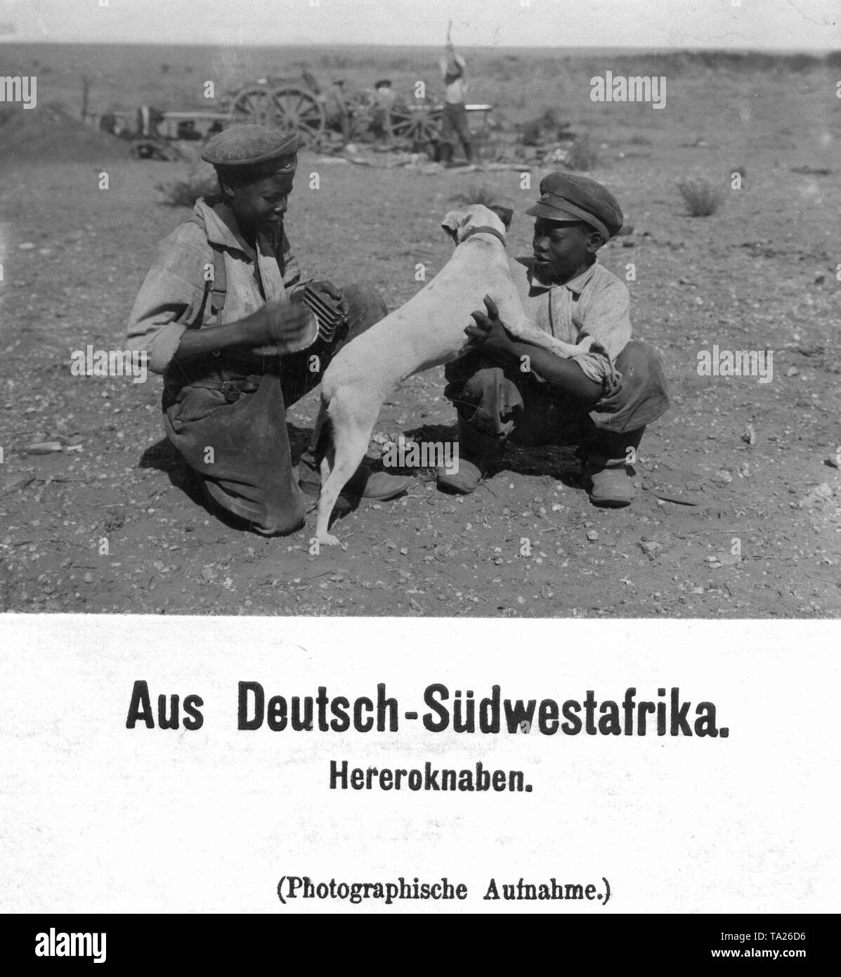 Two boys of the Herero in European clothes play with a dog in the open field. In the background men are working. In German Southwest Africa (undated photo). Stock Photo