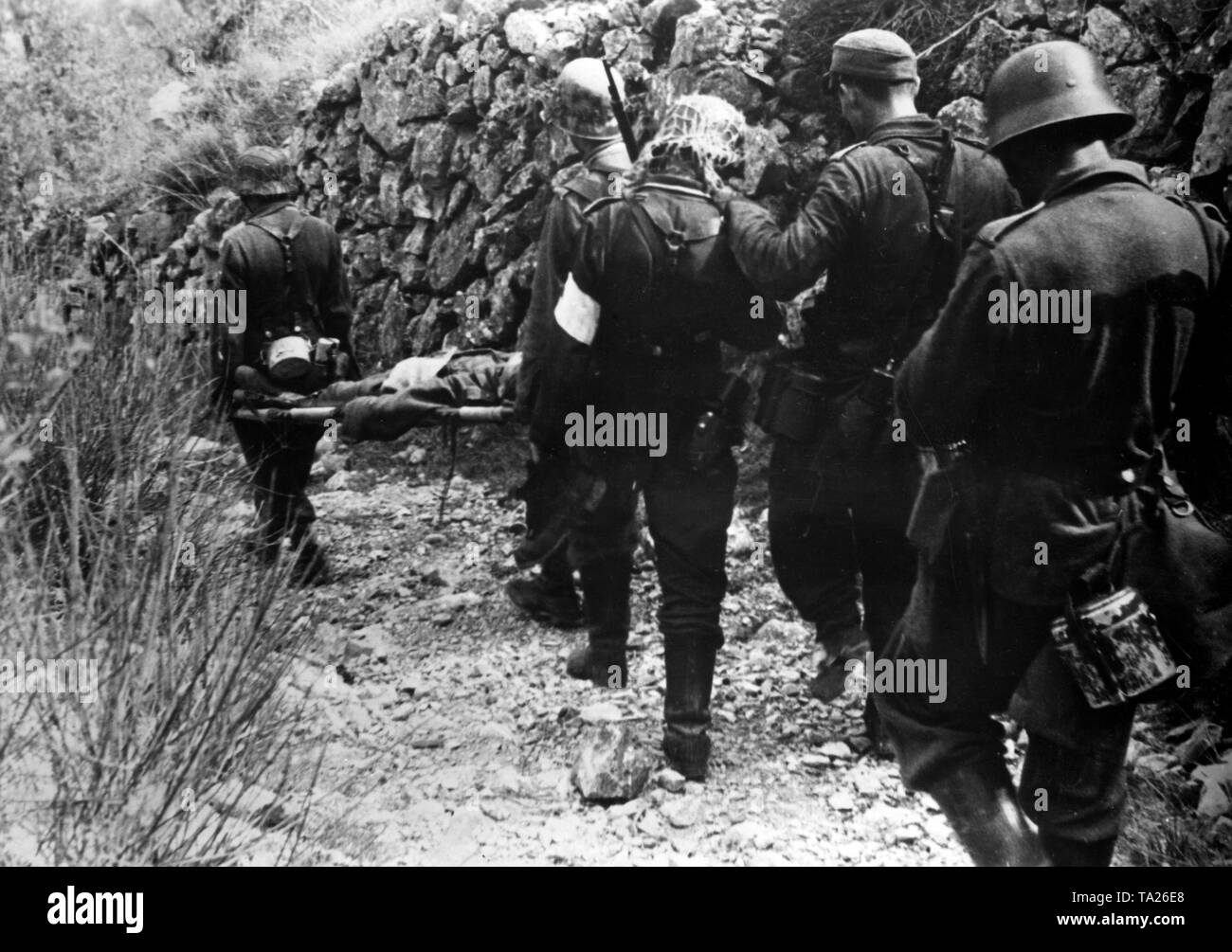 German soldiers carry a wounded comrade down the slope to the main dressing station. Photo of the Propaganda Company (PK): War correspondent Gebauer. Stock Photo