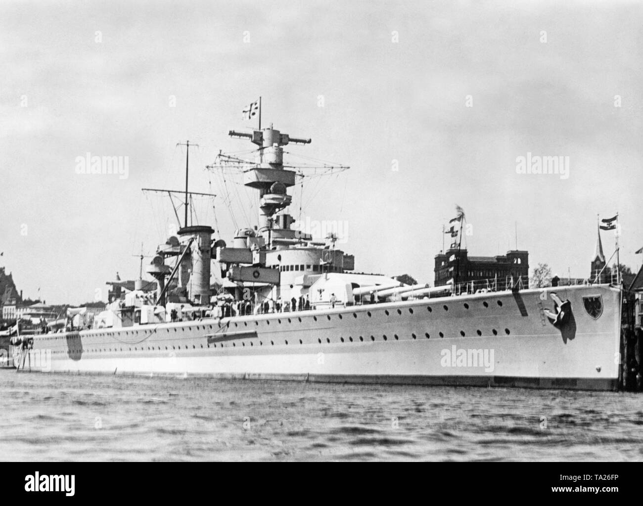 Picture of the German cruiser Deutschland before 1935 in the Kieler Foerde before 1935. In front and behind are two gun turrets with six 28cm Schiffskanone. The German naval ensign (Goesch) of the German Reich (1933-1935 without the swastika) blows in front and behind. - Stock Image