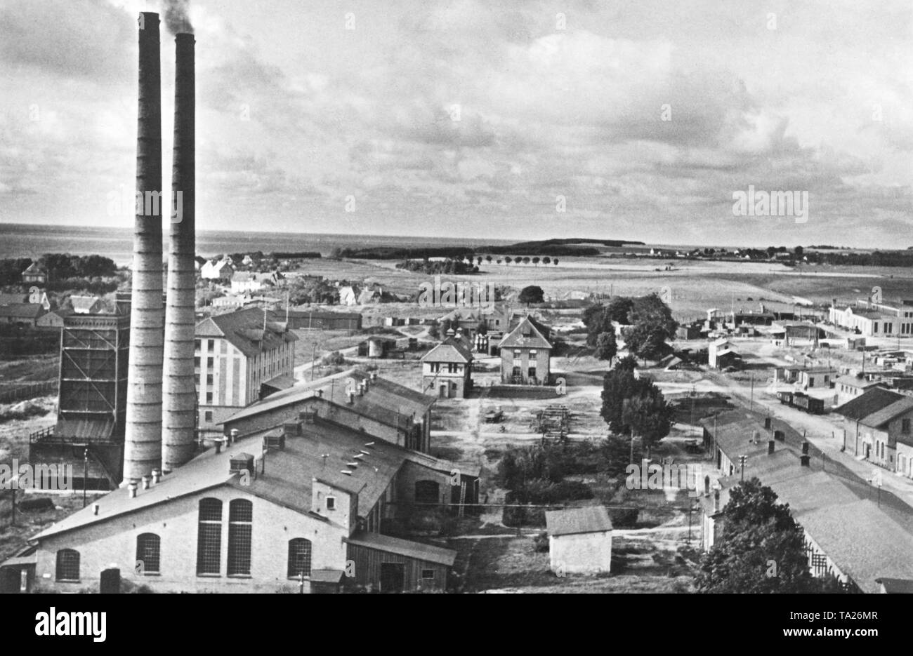 View of a factory premises for amber processing in East Prussia / Germany. The picture shows a building with chimney and other factory buildings. - Stock Image