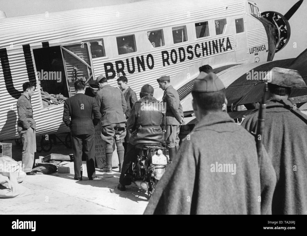 Photo of a German Junkers Ju 52 of the Deutsche Lufthansa AG 1939 at Salamanca airport, Castile and Leon, Spain. The aircraft bears the name 'Bruno Rodschinka '. It is just being loaded. In the foreground, two policemen of the Guardia Civil. - Stock Image