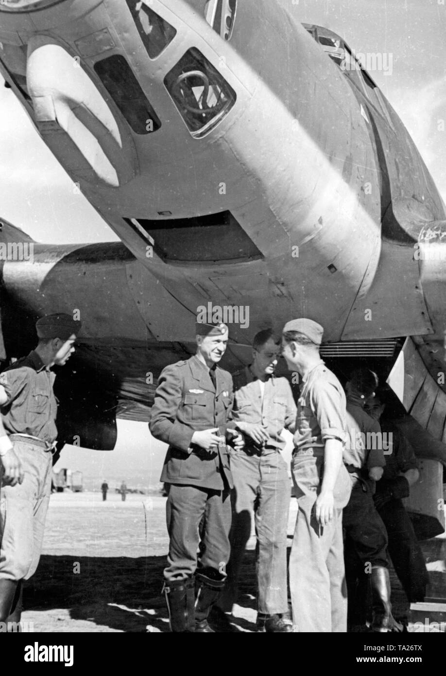 Photo of a Major of the Combat Group 88 of the Condor Legion in conversation with soldiers of the ground personnel at an airfield in Spain. The soldiers are standing under the hull of a Heinkel He 111 bomber. In the upper edge of the photo, the forward gunner compartment, which was made of plexiglass. - Stock Image