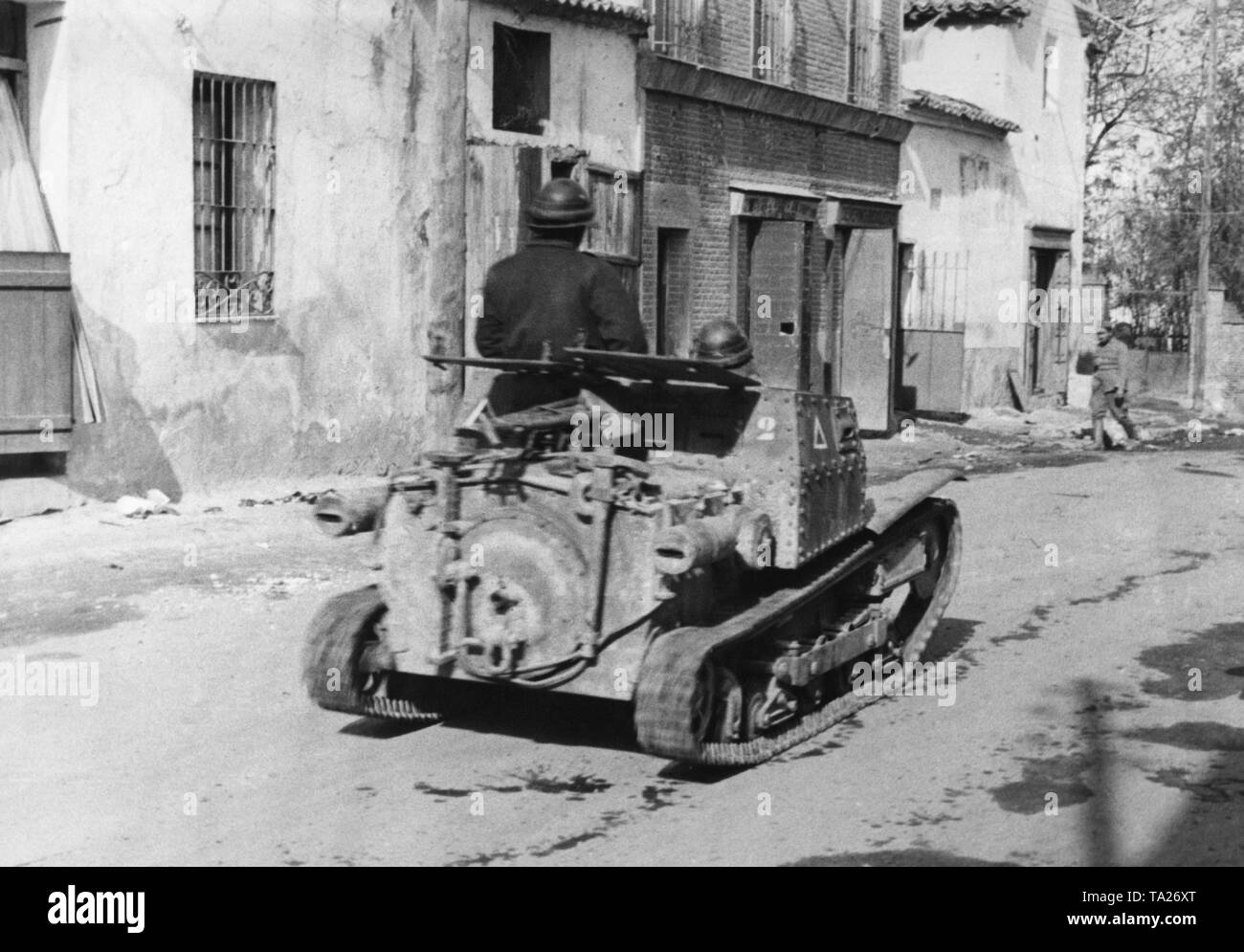 Photo of the rear of an Italian two-man tank (L3 / 33, Carro Veloce 33) of the Corpo Truppe  Volontarie (CTV), passing through the center of Villaverde del Rio, north of Seville. The crew wears leather helmets. Stock Photo