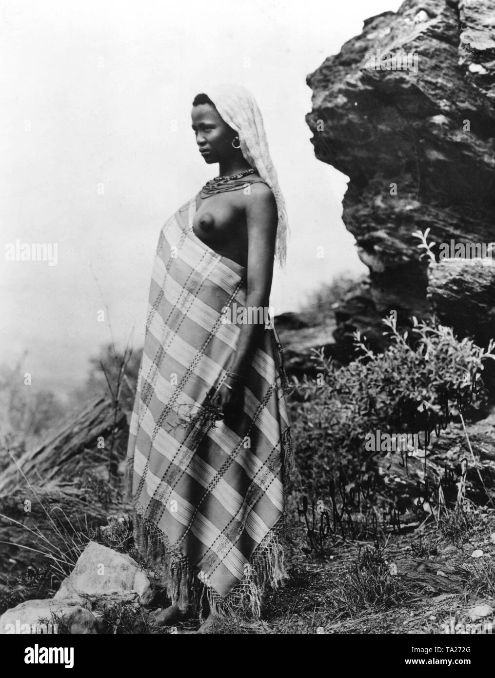 Kaffir woman dressed in a blanket in front of a ledge in German South-West Africa (undated image). - Stock Image