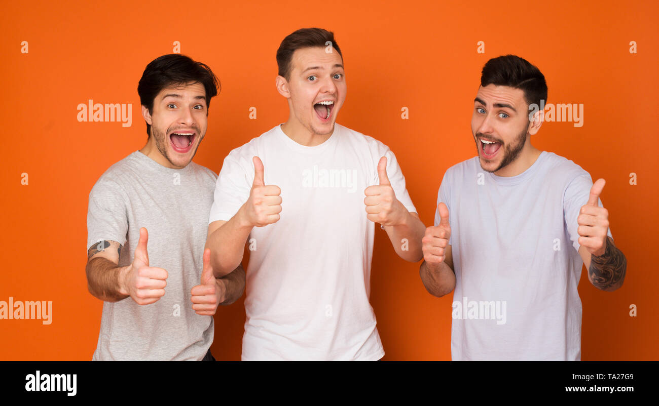 We Recommend! Happy Mates Showing Thumbs Up - Stock Image
