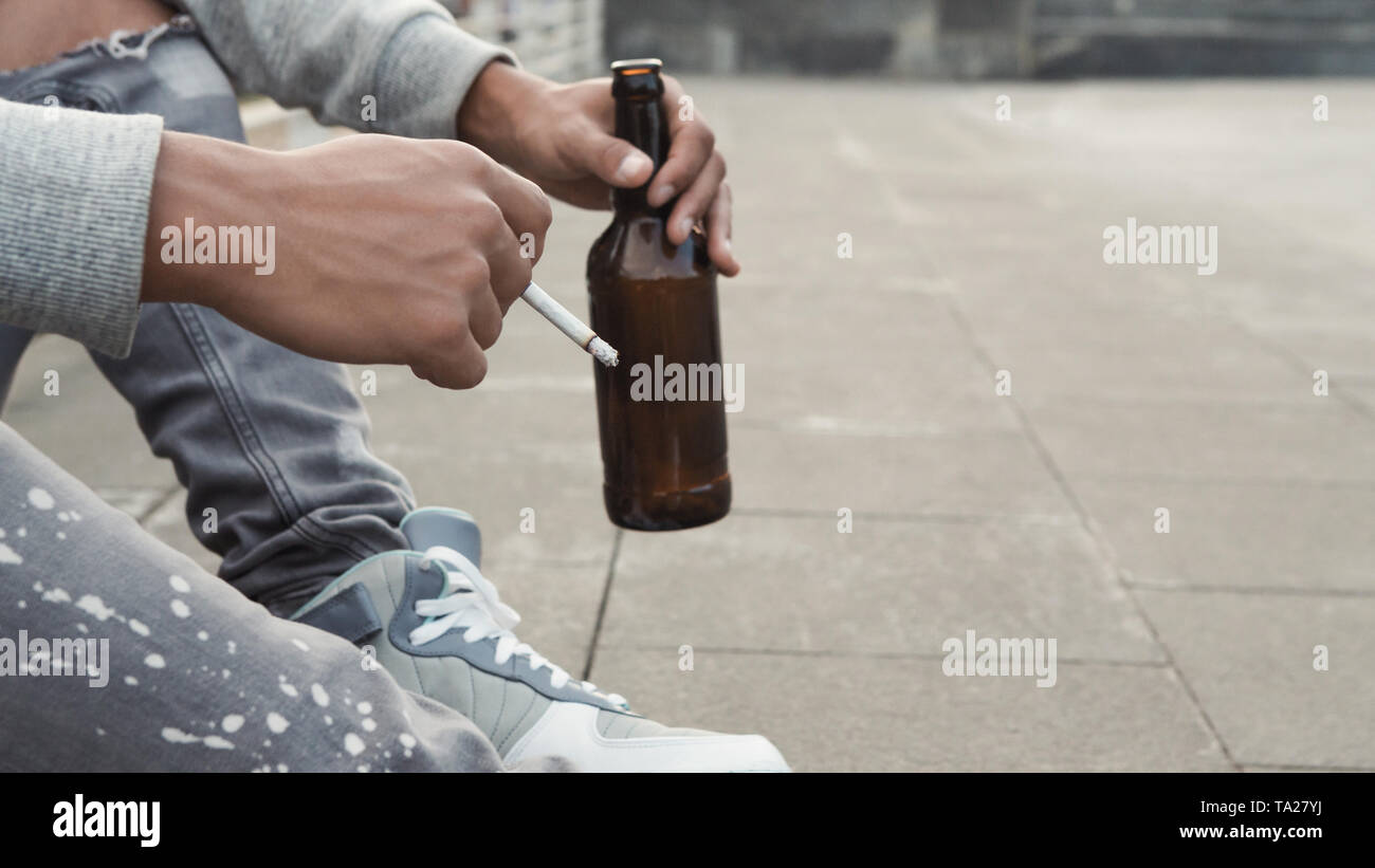 African teen guy sitting alone with cigarette and bottle of beer - Stock Image