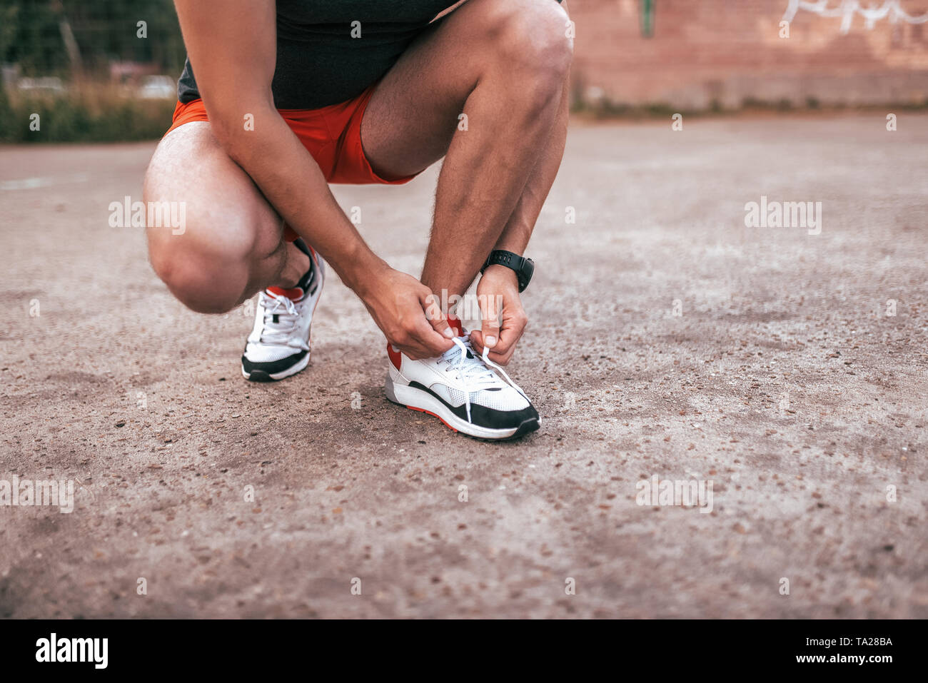 A man athlete tying shoelaces on shoes, training, fitness workout jogging. Summer city background of athletic field. Active lifestyle of youth, close - Stock Image