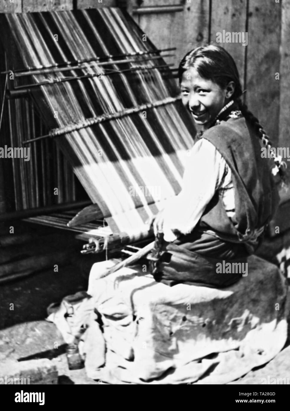 A young girl weaving carpet. - Stock Image