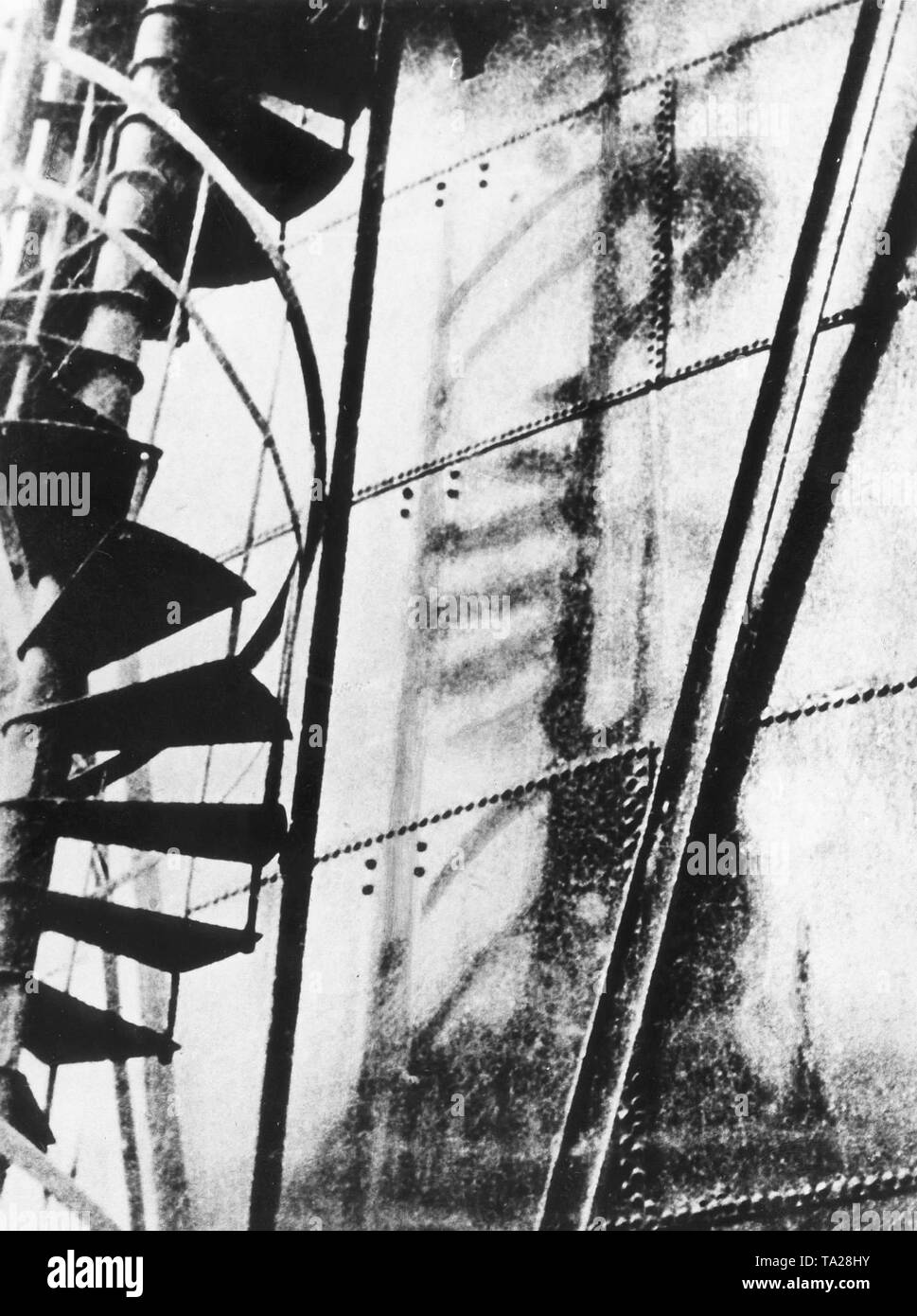 The flash of the atomic bomb explosion has left the shadow of a spiral staircase in an iron wall. Stock Photo