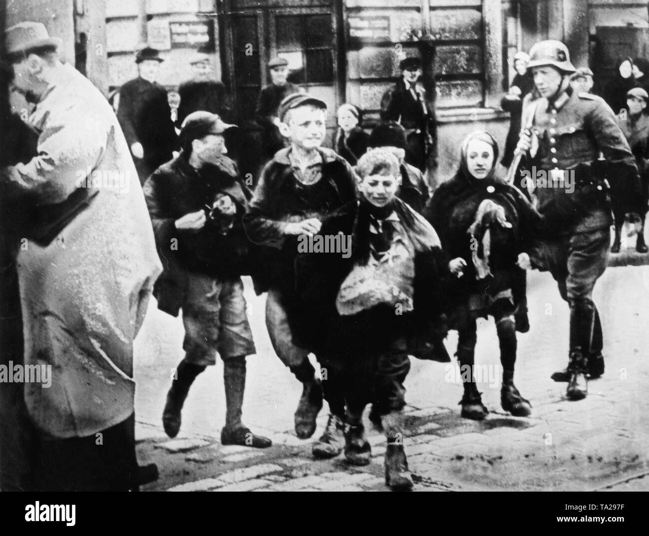 A police officer arrests children who are alleged to have smuggled food into the ghetto - Stock Image