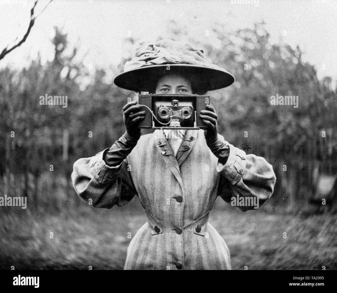 A woman presents the 'No. 2 stereo Brownie camera', which appeared in 1908 as a novelty on the photographic market. - Stock Image