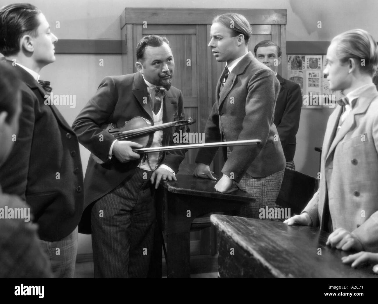 Oskar Sima (middle left) and Heinz Ruehmann (middle right) in the movie 'So ein Flegel' by Robert Stemmle. The comedy is the first film adaptation of the novel the 'Feuerzangenbowle'. In this film Ruehmann plays the brothers Pfeiffer who switch roles. In the last scene they stand together on the stage. - Stock Image