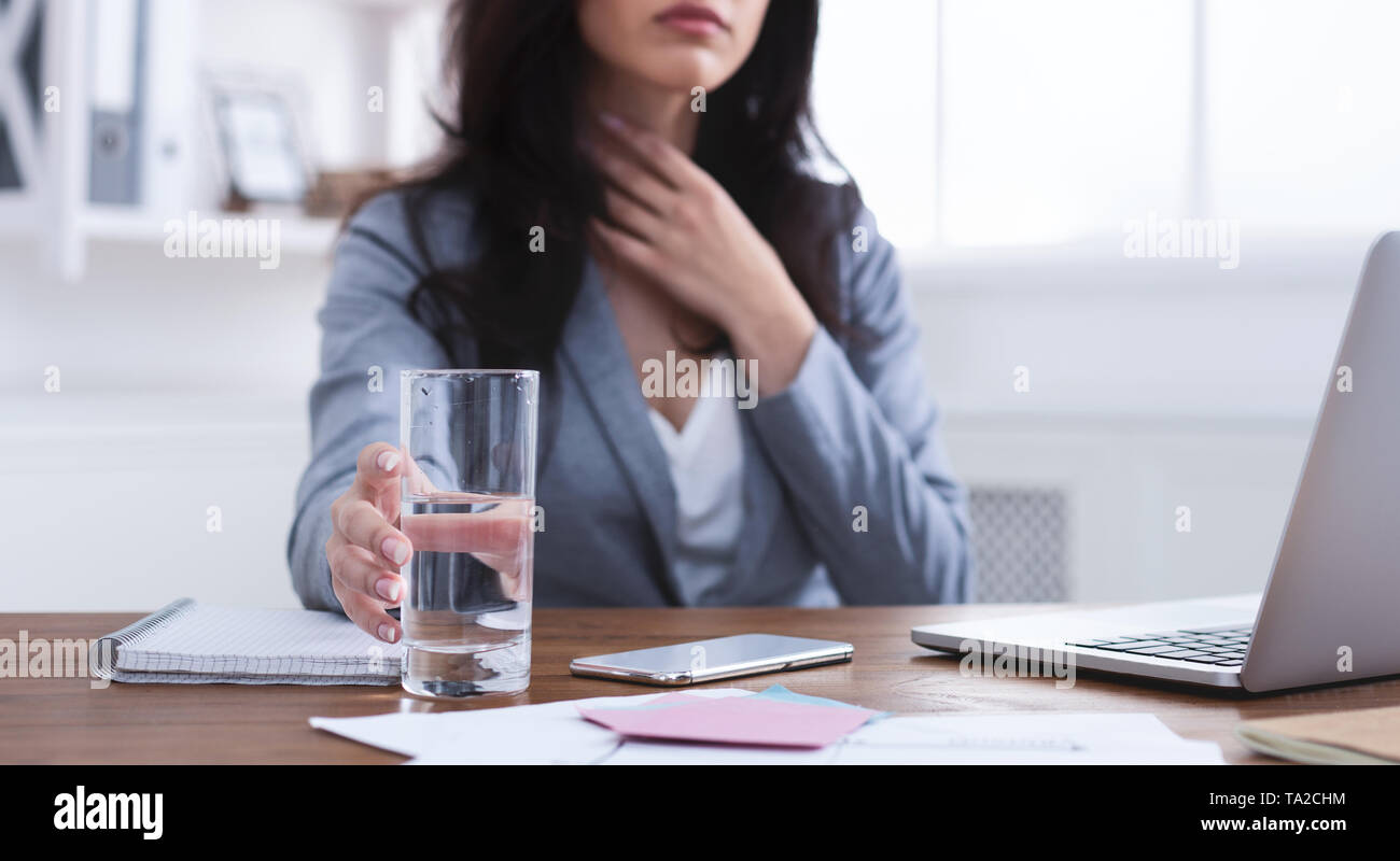 Businesswoman With Sore Throat Drinking Water In Office - Stock Image
