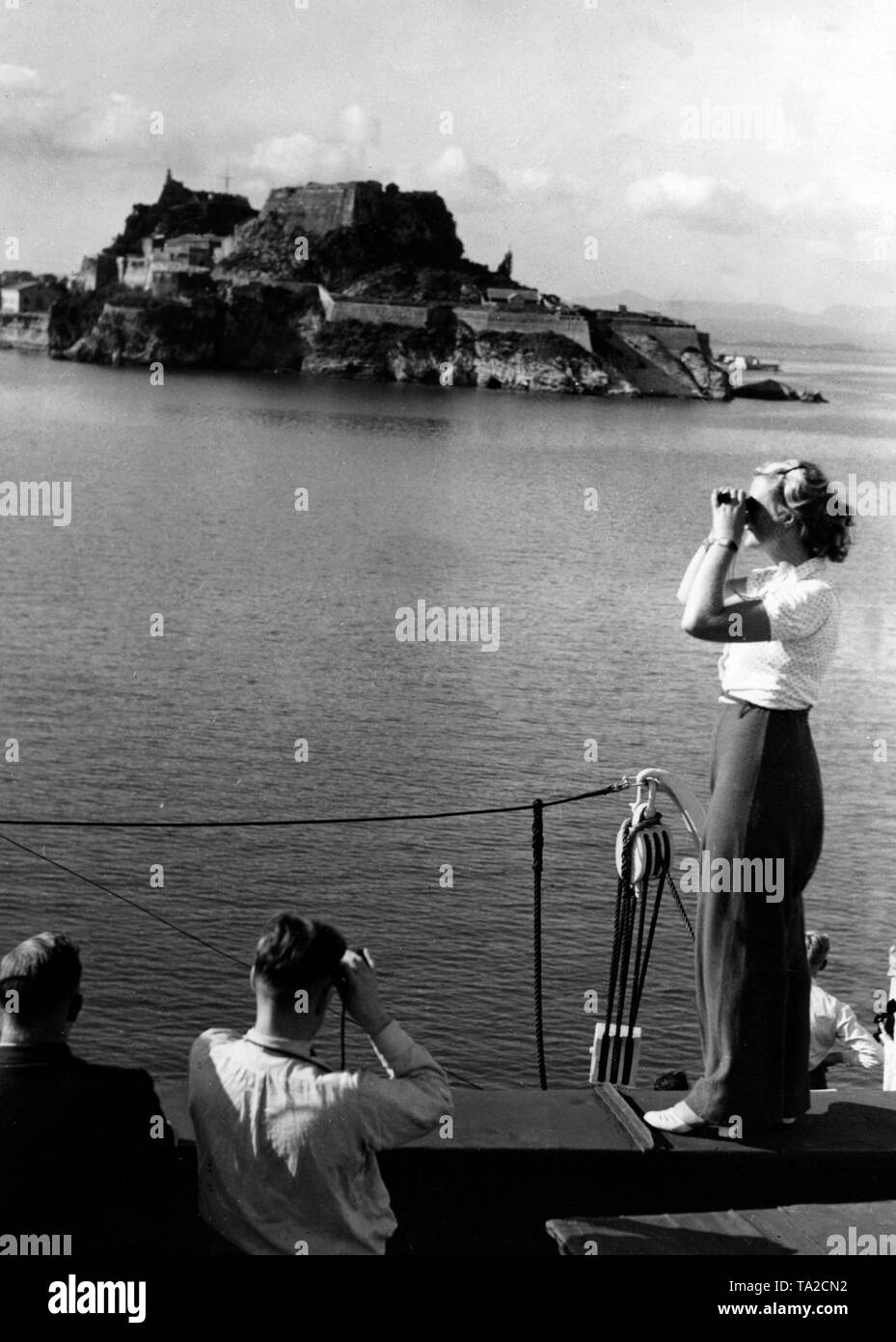 The cruise ship 'Oceana' passes by the island of Corfu on the first sea voyage of the Nazi organization 'Strength through Joy' to Yugoslavia and Greece. The passangers are viewing the island with binoculars. - Stock Image